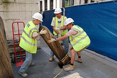 One of the timber bollards being carefully removed to make way for scaffolding access around the base of the column