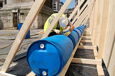 The blue barrels are filled with water to be used as Kentledge (ballast) against wind resistance for the hoarding