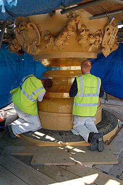 Gold leaf being applied to the flaming orb. Note that hard hats are not being worn as it is sometimes necessary to get your head close to the work to ensure the leaf is adhered properly.