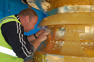 The gold leaf gilding is very carefully applied onto the prepared copper orb