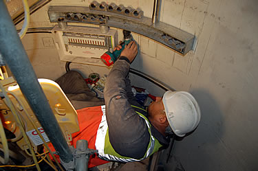 The electrician foreman Simon hard at work inside the Monument. Notice how the stainless steel conduits, boxes and fixings are all individually shaped to fit exactly the curvature of the internal walls.