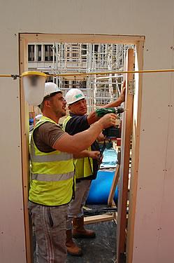 Carpenters installing pedestrian access door to site